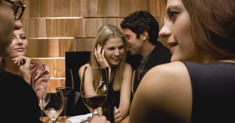 Young man whispering in woman's ear at party