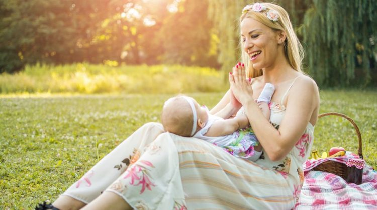 Mother holding baby on lap and clapping hands to make her happy. They are enjoying together beautiful summer day in the nature.