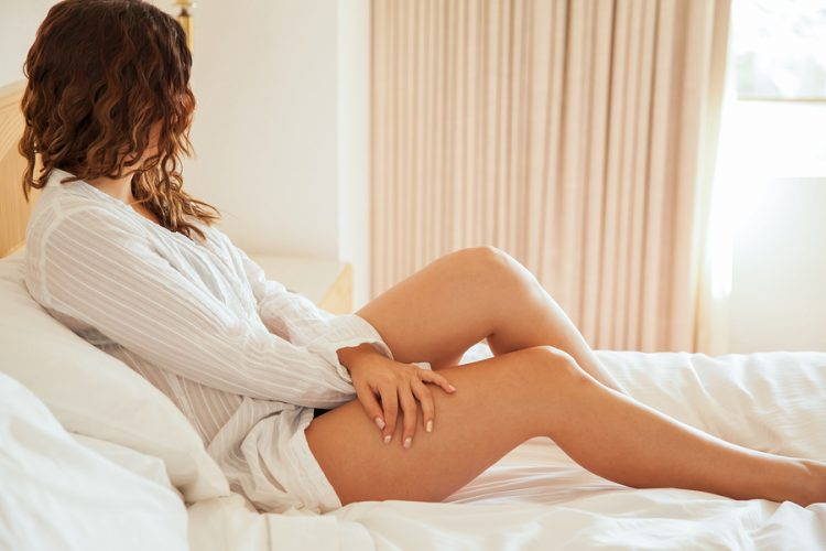 Profile view of a sexy young woman wearing a shirt over her underwear and relaxing in a bed